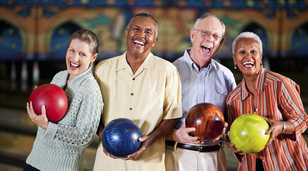 Multi-ethnic senior couples (50s, 60s) having fun in bowling alley.